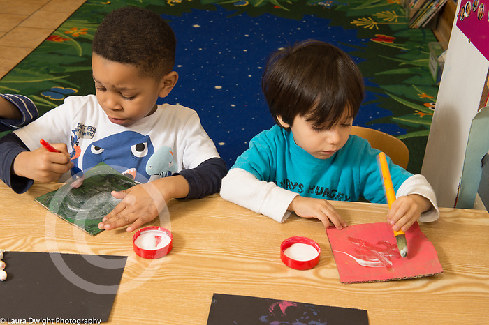 Education Preschool 4 year olds art activity gluing or painting two boys sitting side by side one using brush with right hand and the other using the left hand
