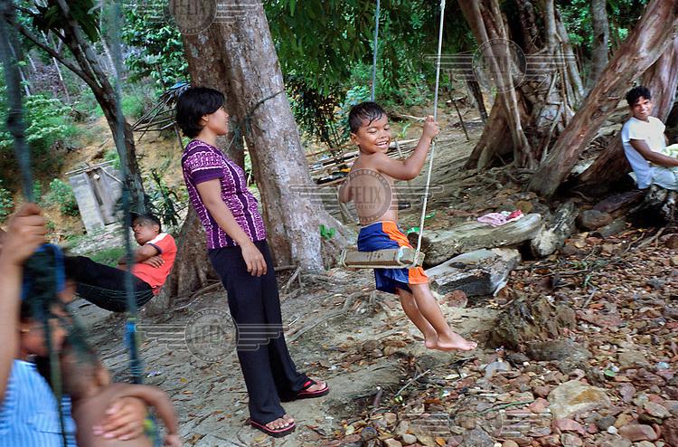 Children playing outside their homes in a slum on Batam island.