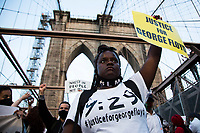 NEW YORK, USA - May 25: A woman in support of Black Lives Matteren holds a banner on the Brooklyn Bridge on the first anniversary of her death on May 25, 2021 in New York City. George Floyd's assassination in Minneapolis sparked a worldwide outcry and continued to propel the Black Lives Matter movement through different cities in the United States and the world. (Photo by Pablo Monsalve / VIEWpress via Getty Images)
