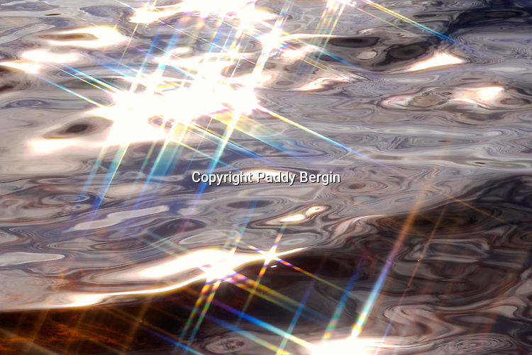 Patterns, colours and sunlight reflections on water.<br />