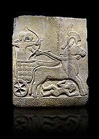 Hittite relief sculpted orthostat stone panel of Long Wall Basalt, Karkamıs, (Kargamıs), Carchemish (Karkemish), 900 - 700 B.C.  Anatolian Civilizations Museum, Ankara, Turkey<br /> <br /> Chariot. One of the two figures in the chariot holds the horse's headstall while the other throws arrows. There is a naked enemy with an arrow in his hip lying face down under the horse's feet. It is thought that this figure is depicted smaller than the other figures since it is an enemy soldier. The tower part of the orthostat is decorated with braiding motifs.<br /> <br /> On a black background.