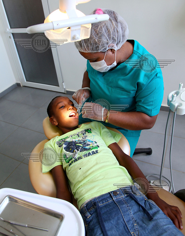 A dentist examines the teeth of a child who is resident at the 'Akkari' centre, a home for abandoned children and orphans. The centre offers a shelter to 225 boys from 5 to 18 years old.