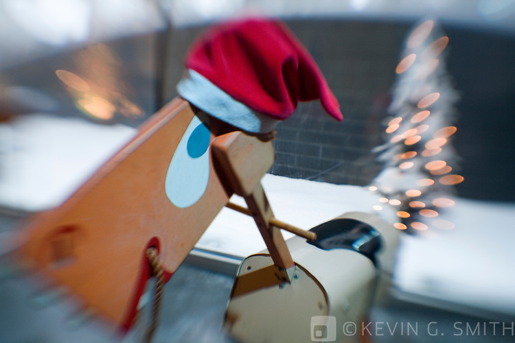 Hand painted 60's retro rocking horse with Santa hat standing in front of modern style home courtyard window with lighted christmas tree in background, selective focus.