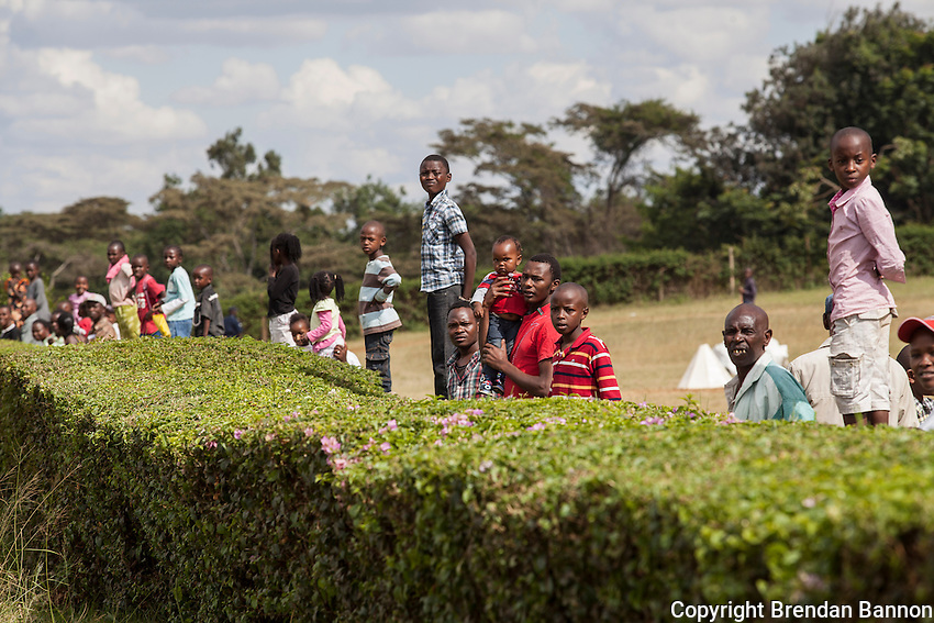 Spectators watch the finish of a race from  the Silvering area of Ngong racecourse. The silvering is an area where people  can watch the races free of charge. There is a large betting area where folks can bet. Ngong Racecourse Nairobi, Kenya. March 17, 2013 Photo: Brendan Bannon