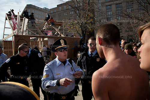 Washington, D.C.<br /> December 4, 2011<br /> <br /> Angry Occupy D.C. protestors confront U.S. Park Police, who are preparing to cordon off a wooden structure the demonstrators errected overnight. <br /> <br /> Summary: Occupy D.C.'s overnight construction of a large wooden structure in McPherson Square ended two months of relatively peaceful coexistence with the U.S. Park Police, who said that the building appeared to be a permanent structure and was therefore illegal. Occupy D.C. said that they were building it to protect themselves from increasingly cold weather. Protesters defied repeated orders to abandon the building and take it down -- setting the stage for a day long standoff -- which ended in 31 arrests and the destruction of the building by the Park Police.