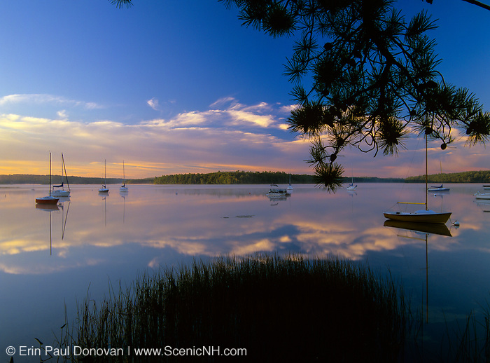 Reflection of sailboats in Lake Massabesic in Auburn, New Hampshire at sunrise. Located in Manchester and Auburn, this lake covers over 2,500 acres, and it is the drinking water supply for the Manchester area.