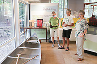 Ozark Society members Beth Keck (from left), chair member Lowell Collins and Lisa Ferguson share a conversation about Dr. Neal Compton's canoe, Monday, August 2, 2021 at Compton Gardens in Bentonville. Compton Gardens kicked off their celebration of Dr. Neal Compton with Dr. Compton Days, a family friendly celebration with events including guided tours, free ice-cream and a screening of the movie The Buffalo Flows, a one-hour documentary about life on the Buffalo River. Dr. Compton fought for 60 years to keep the Buffalo River from being damned. Next year, the Buffalo River will celebrate 50 years since its designation as a national river. Check out nwaonline.com/210803Daily/ for today's photo gallery. <br /> (NWA Democrat-Gazette/Charlie Kaijo)