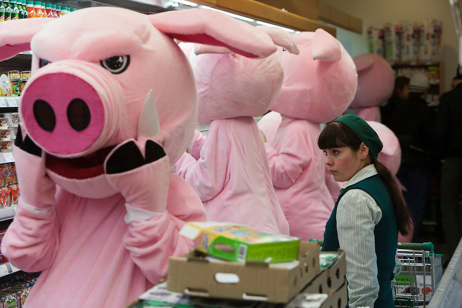 Moscow, Russia, 03/03/2011..A shop assistant watches as members of health campaign group Pigs Against check the sell-by dates and quality of food in a city centre supermarket while dressed in pig costumes.