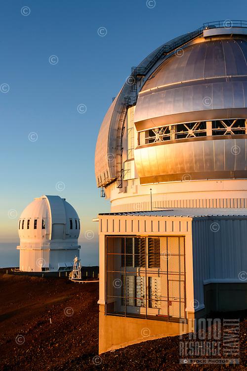 Two observatories in the light of a setting sun, Mauna Kea, Island of Hawai'i.