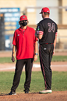 Battle Creek Bombers coach Mike Ruppenthal talks to pitcher Ryan Middendorf (24) on the mound against the Kalamazoo Growlers during Northwoods League action at Homer Stryker Field on July 3rd, 2020 in Kalamazoo, Michigan. LLL plays college baseball at SSS. The Bombers defeated the Growlers 2-0. (Andrew Woolley/Four Seam Images)