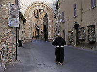 Franciscan Friar reading newspaper walks along Via S. Chiara toward city gate in Assisi, Ital