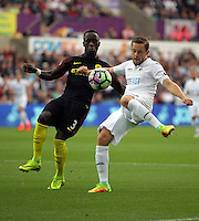 Gylfi Sigurdsson of Swansea City (R) crosses the ball past Bacary Sagna of Manchester City during the Premier League match between Swansea City and Manchester City at The Liberty Stadium in Swansea, Wales, UK. Saturday 24 September 2016