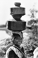 India, Narmada River, Narmada dams and protest movement of NBA Narmada Bachao Andolan, movement to save the Narmada river, and affected Adivasi in their villages, woman carry water in pots on her head