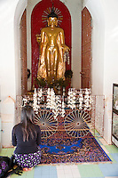Myanmar, Burma, Shwezegon (Shwezigon) Pagoda, near Bagan.  Young Woman with Backpack Kneels in front of Buddha Statue.  Eleventh-Century Indian influence can be seen in the face and robe design of this Buddha.