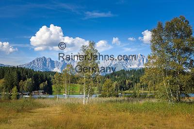Austria, Tyrol, Reith near Kitzbuhel: nature reserve at idyllic Schwarzsee (Black Lake) on the outskirts of Kitzbuhel, at background Wilder Kaiser mountains | Oesterreich, Tirol, Reith bei Kitzbuehel: Naturschutzgebiet am Schwarzsee, idyllisch gelegener Badesee, 8 ha gross und bis zu 8 m tief, einer der waermsten Seen der Alpen, im Hintergrund das Wilder Kaiser Gebirge