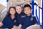 Vietnamese girl and Vietnamese boy and Caucasian girl all seven years old sit.together on top of slide on playground at school