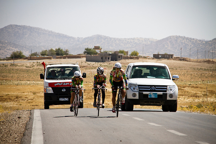 SULAIMANIYAH, IRAQ: Members of Newroz cycling club compete in team time trials in temperatures of over 30ºC.  One of the team, Lavan, had a puncture and had to fall back and fix it before completing the time trial. Nyan Yassin is far left.<br /> <br /> Nyan Yassin, 24, is a professional competitive cyclist in Sulaimaniyah in the semi-autonomous region of Iraqi Kurdistan.  She is the captain of an all-female club called Newroz Club, which is the only cycling club for women in Sulaimaniyah, although there are other clubs around Iraq.  She trains and competes on roads that are badly surfaced and busy with traffic.<br /> <br /> Nyan was the first woman to start cycling in Sulaimaniyah.  She was always competitive and after trying her hand at different sports she settled on cycling.  She is now the top female cyclist in Iraq.  Her nickname is MigMig after the noise made by the cartoon character Roadrunner.<br /> <br /> Despite being clearly talented at her sport Nyan knows that in a couple of years she will have to get married and then abandon it as, in the traditional society that Kurdistan is, being a wife and a competitive sportswoman at the same time is not an option.<br /> <br /> Photo by Gona Hassan/Metrography