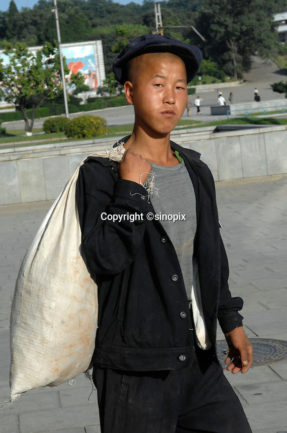"A poverty-stricken man in PyongYang, North Korea. The DPRK (Democratic People's Republic of Korea) is the last great dictatorship where the people are bombarded with images of the ""Eternal President"" Kim Il-sung who died in 1994 and his son and current leader Kim Jong-il who are worshipped like a God."