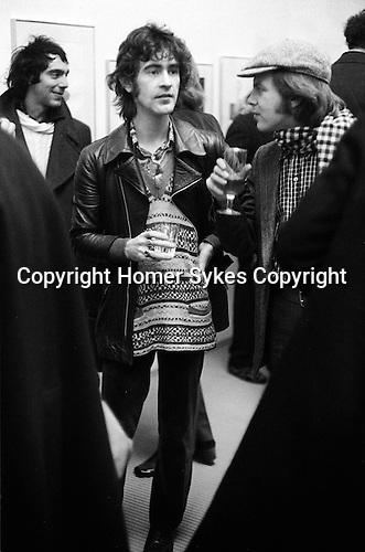 "Ossie Clark at a David Hockney private view, ""Recent Etchings"" at the Kasmin Gallery Bond Street London.  December 1969.<br /> Derek Jarman artist seen behind Ossie to left."