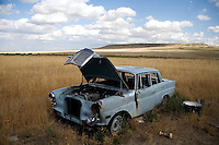 An old, broken and abandoned car sits in a field under a cloudy sky outside Great Falls, Montana, USA.