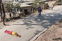 Nepal, Kathmandu, Swayambhunath.  A Worshiper Making his way around the base of the Stupa lies prostrate in the roadway.