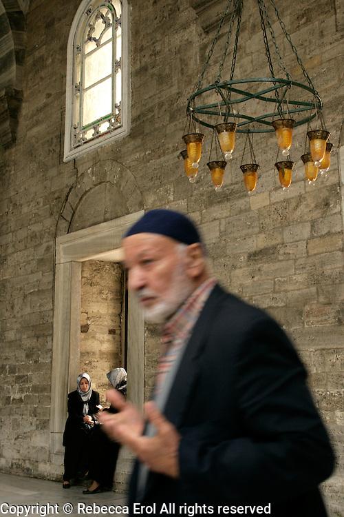 Eyup mosque, istanbul, Turkey: man passes on his way to prayer