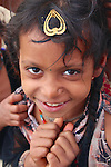Amongst the crowds and chaos of the Maha Kumb Mela, this young girl had time for a smile.