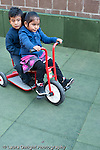 Education preschool outside at playground boy and girl riding tricycle together vertical