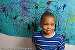 Preschool ages 3-5 portrait of smiling boy with colorful artwork behind him horizontal