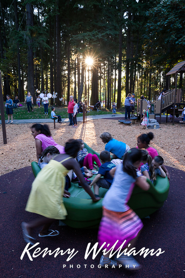 Children playing on merry go round at sunset, Dottie Harper Park, Burien, Washington State, WA, America, USA.