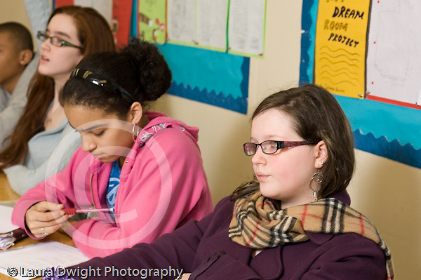 Public Middle School Grade 8 female students listening in class horizontal