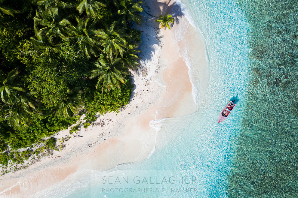 A boat sits offshore from an island in the Funafuti atoll. Tuvalu. March, 2019.
