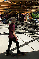 01 JUL 2014 - CHICAGO, USA - A skateboarder waits to cross the road under the tracks of the elevated train system, The L, at the Wells Street and West Wacker Drive junction in Chicago in the USA (PHOTO COPYRIGHT © 2014 NIGEL FARROW, ALL RIGHTS RESERVED)