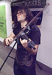 Michael Shulman playing in Union Square Subway Station, NYC.  Yes, that is a Dragon with glowing eyes at the end of the violin.  Michael is a self-described Neo-Classical Shred Violinist.    He is very good and original.  www.blackviolin.com