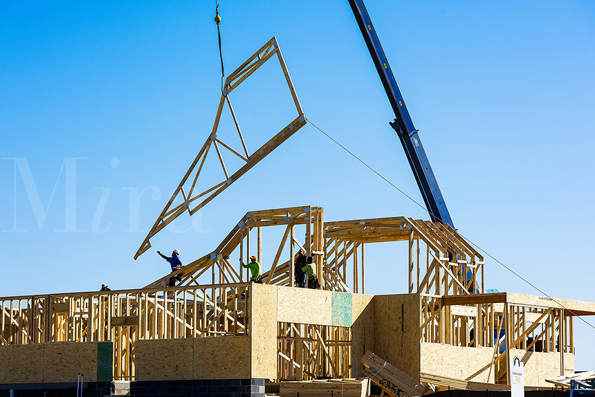 Workers place prefabricated pieces in new house construction.