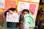 Educaton preschool  3-4 year olds art activity two girls holding up drawings they made with markers covering their faces horizontal recognizable shapes