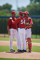 GCL Nationals pitching coach Larry Pardo (54) talks with pitcher Pedro Gonzalez (26) and catcher Geraldi Diaz (12) during a Gulf Coast League game against the GCL Astros on August 9, 2019 at FITTEAM Ballpark of the Palm Beaches training complex in Palm Beach, Florida.  GCL Nationals defeated the GCL Astros 8-2.  (Mike Janes/Four Seam Images)
