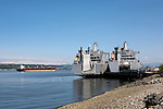 Military Transports supporting Fort Lewis (Joint Base Lewis McChord) wait to load in Tacoma, WA.  Commencement Bay with the Cascade Mountains in background, as seen from the south shore and Foss Waterway.  Commencement Bay's history of industry and shipping has led it to designation as a Superfund Cleanup Site and one of the most polluted waterways in the nation.  Commencement Bay Nearshore/Tideflats (CB/NT) Superfund Site.  Ironically viewed from the Peace Pagoda.