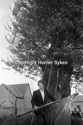 Arbor Day. Aston-on-Clun, Shropshire 1975. The custom of dressing a tree with flags survives from an ancient era when it was done in worship of Bridget, goddess of fertility. Later sanctified as St Bridget or St Bride, the goddess had a tree for a shrine. Hopesay Parish Council now finances the custom from the rates. In 1975 twenty-five pounds was given to buy nine flags that are used to decorate the Black Poplar every 29 May.