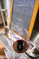 Mourvedre. Chateau Grand Moulin. In Lezignan-Corbieres. Les Corbieres. Languedoc. Sign on tank. Stainless steel fermentation and storage tanks. France. Europe. Wine glass.