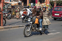 Jaipur, Rajasthan, India.  Mid-day Street Traffic in Central Jaipur.  Old Man Getting a Ride on a Motorbike.