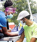 WATERBURY, CT. - 20 July 2021-072021SV01-Sabrina Cosby, RN, gives a vaccine to John Quiles-Soto of Waterbury at a Police Activity League back-to-school vaccine event at the PAL Park in Waterbury Tuesday.<br /> Steven Valenti Republican-American