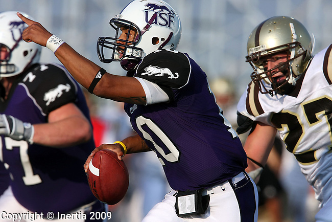 SIOUX FALLS, SD - SEPTEMBER 5:  Lorenzo Brown #10 of the University of Sioux Falls point to a receiver while being chased by Phil Harm #27 of Nebraska Wesleyan in the first quarter of their game Saturday evening at the USF Sports Complex. (Photo by Dave Eggen/Inertia).