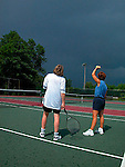 Tennis players watch approaching storm