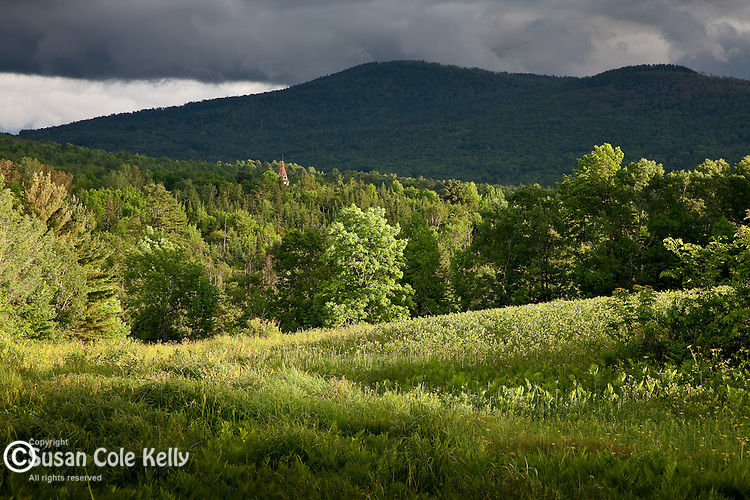 The steeple of the Sugar Hill Meetinghouse peeks above the trees at sunset in Sugar Hill, NH, USA
