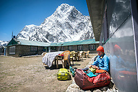 A trekker at a Nepali guesthouse organizes her duffel bags, with the mountain Cholatse above, Dzongla, Nepal.