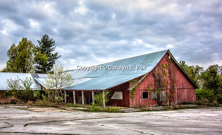 An old barn sits in a parking lot.
