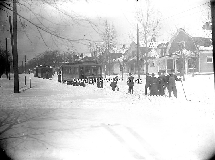 SNOWBOUND TROLLEYS ON THE HAVELOCK LINE. A crew of streetcar workers with shovels, led by a giant man in overalls, clear the way for the Havelock trolley. Havelock was an independent town northeast of Lincoln from 1893 to 1930, built around a large shop facility of the Burlington Railroad. It remains a distinctive neighborhood with a very active Burlington yard.<br /> <br /> Photographs taken on black and white glass negatives by African American photographer(s) John Johnson and Earl McWilliams from 1910 to 1925 in Lincoln, Nebraska. Douglas Keister has 280 5x7 glass negatives taken by these photographers. Larger scans available on request.