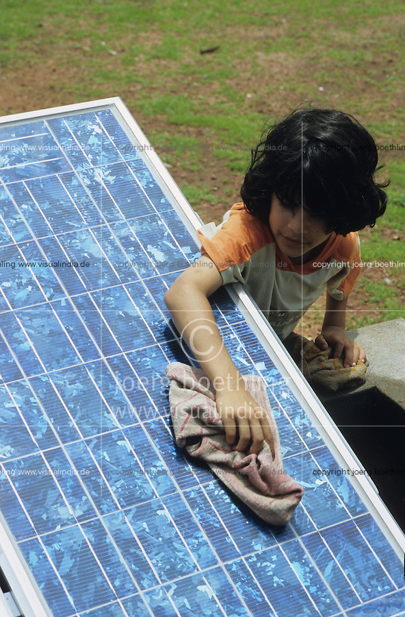 Indien Karnataka, Junge reinigt Shell Solarzellen in Solar workshop / India Karnataka, cleaning of solar cell in solar workshop