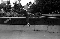 """A skateboarder falls at a trick attempt. The graffiti on the wall reads """"Gotov Je"""", meaning """"He is Finished,"""" referring to the end of Slobodan Miloshevic. Belgrade, Serbia, Yugoslavia<br />"""